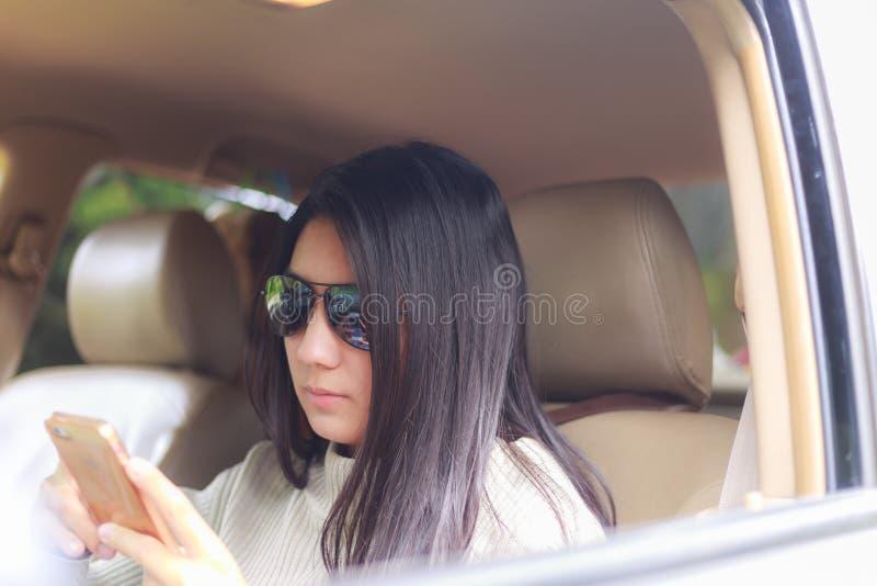 Mulher asiática que joga o smartphone no carro preto fotografia de stock