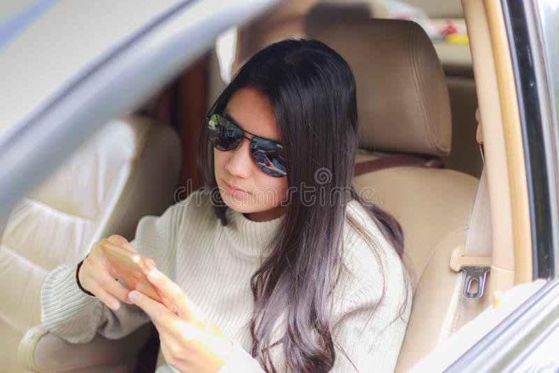 Mulher asiática que joga o smartphone no carro preto fotos de stock