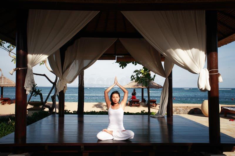 Mulher asiática que Meditating pela praia