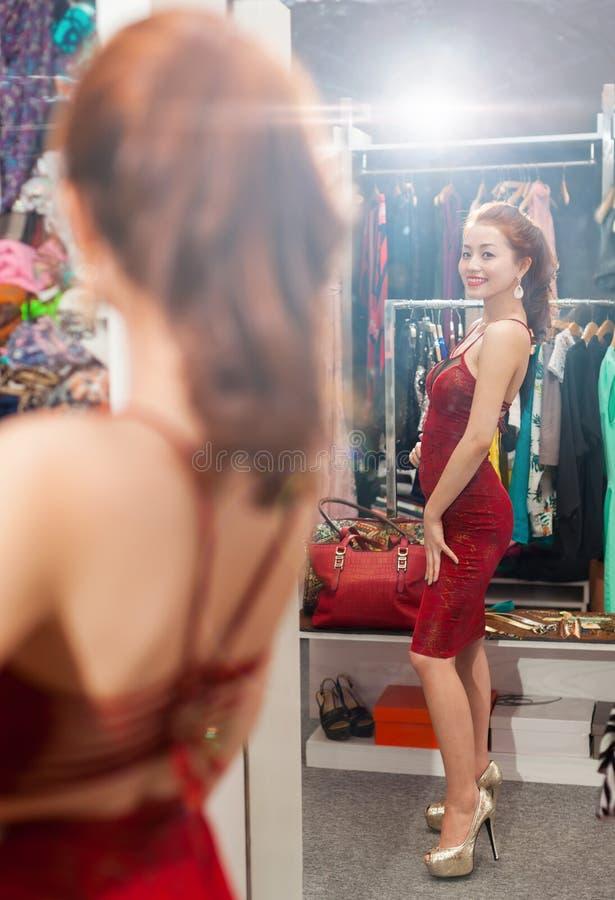 Mulher asiática que olha a escolha da compra do espelho fotografia de stock