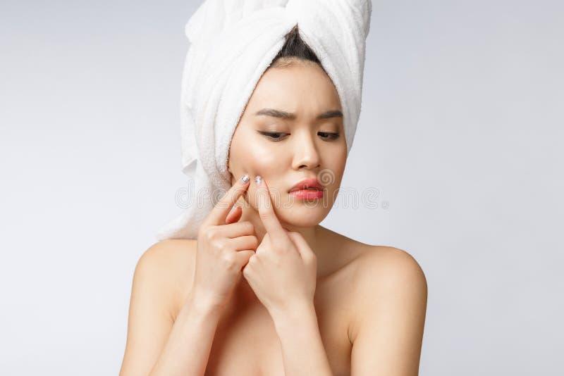 Mulher asiática que olha a espinha na cara A jovem mulher tenta remover sua espinha Conceito do cuidado de pele da mulher Isolado imagem de stock