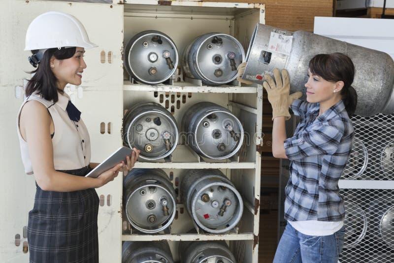 Mulher asiática que olha o cilindro levando fêmea do propano do trabalhador industrial fotografia de stock