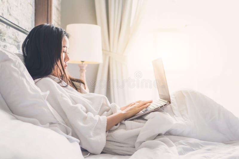 Mulher asiática que relaxa na sala de hotel e que trabalha no labtop, imagens de stock