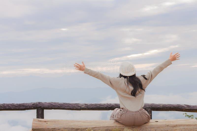 Mulher asiática que relaxa sobre uma montanha imagem de stock