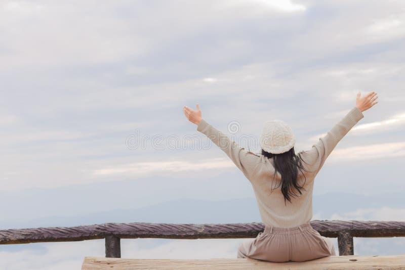Mulher asiática que relaxa sobre uma montanha imagens de stock