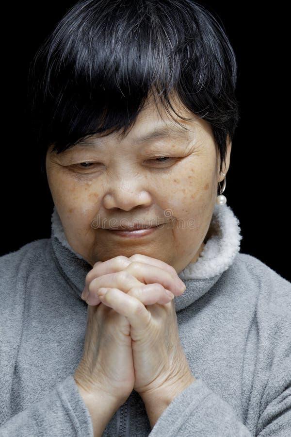 Mulher asiática que reza e que elogia o senhor imagem de stock