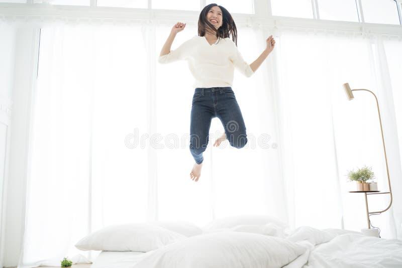 Mulher asiática que salta na cama Conceito feliz foto de stock