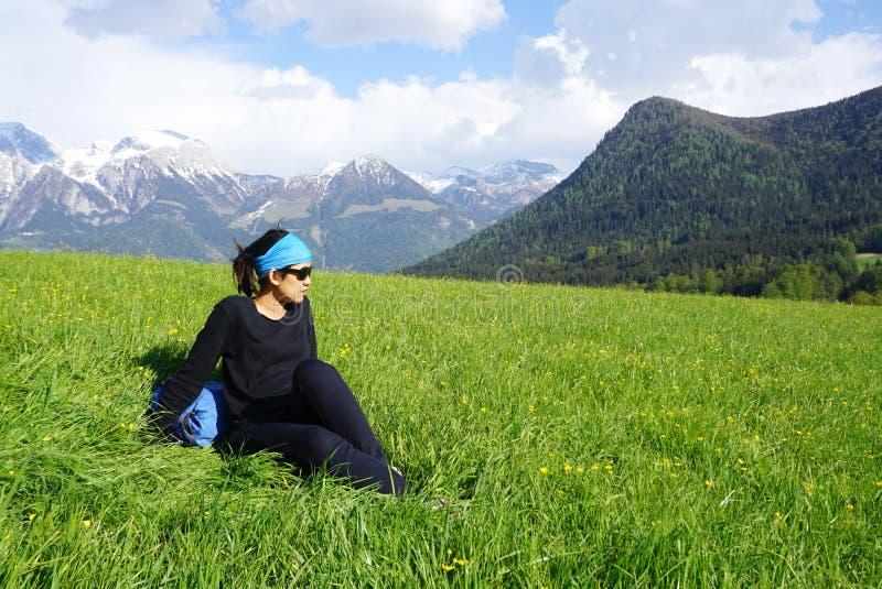 Mulher asiática que senta-se na grama com a montanha bonita no imagens de stock royalty free