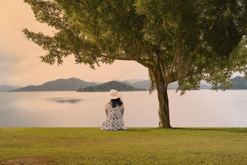 Mulher asiática que senta-se na terra imagens de stock