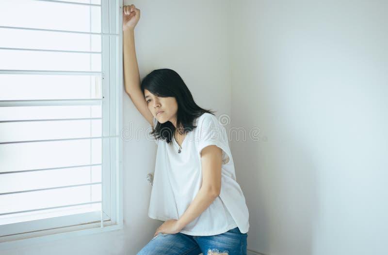 Mulher asiática que senta-se no quarto em casa, no problema infeliz e confuso do sentimento fêmea na vida pessoal, conceito inesp imagem de stock royalty free