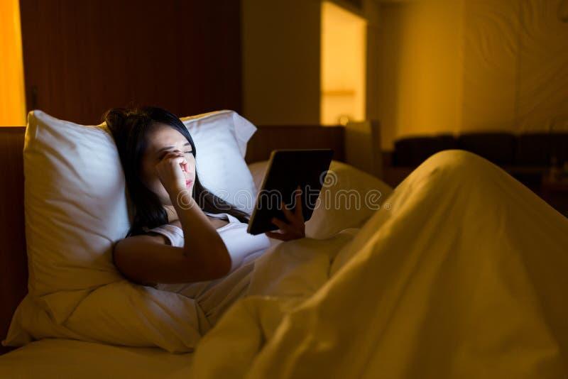 Mulher asiática que sente cansado em usar a tabuleta digital em casa imagens de stock
