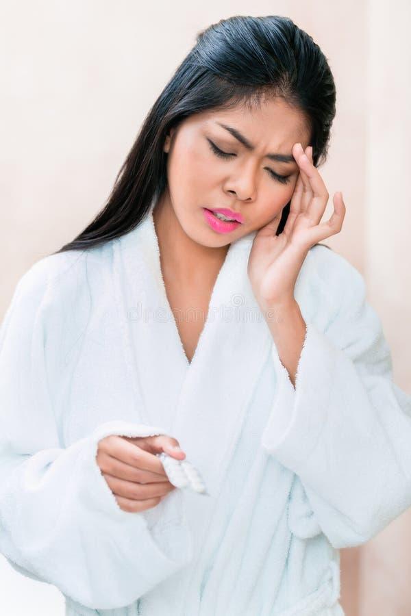 Mulher asiática que toma analgésicos para a dor de cabeça imagem de stock