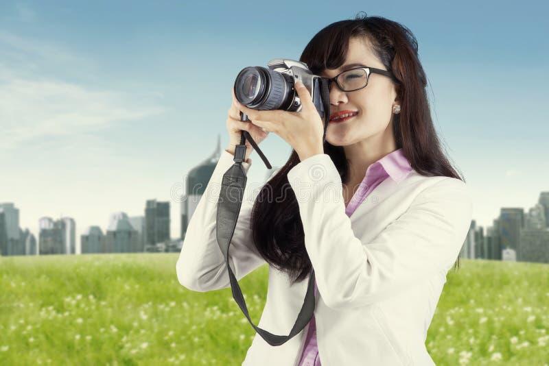 Mulher asiática que toma a imagem usando a câmara digital foto de stock