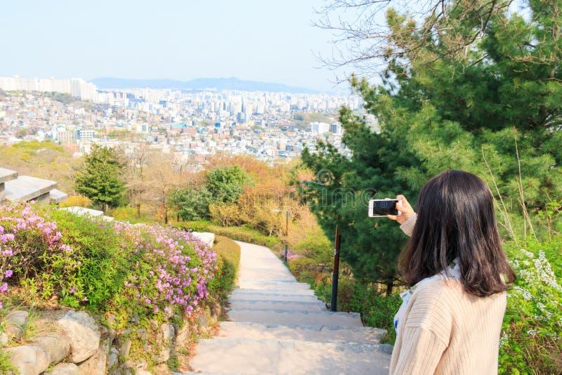 Mulher asiática que toma imagens da vista aérea da cidade de Seoul com smartphone imagens de stock royalty free