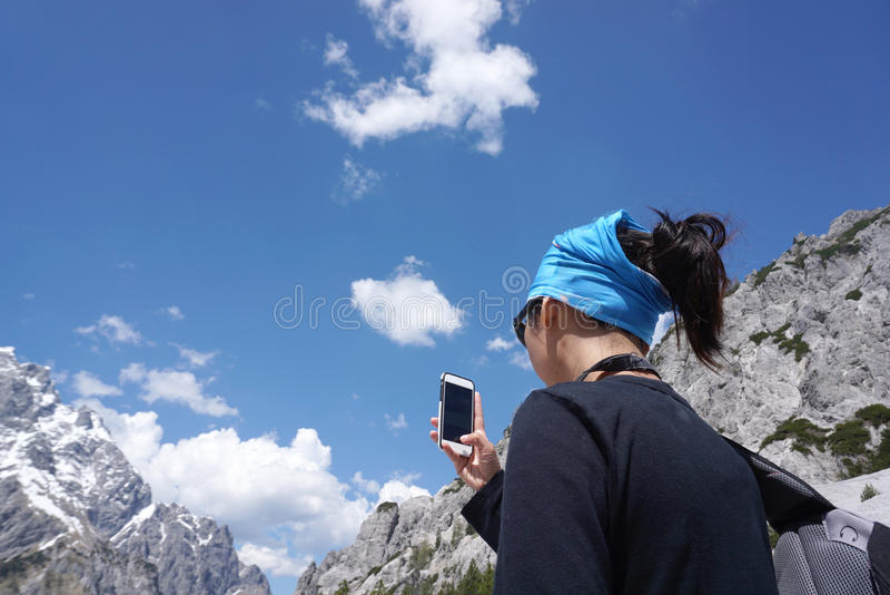 Mulher asiática que toma uma foto com o telefone esperto do MOU bonito imagens de stock