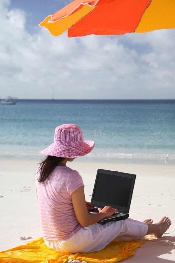 Mulher asiática que trabalha na praia imagem de stock
