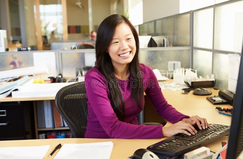 Mulher asiática que trabalha no computador no escritório moderno fotos de stock royalty free