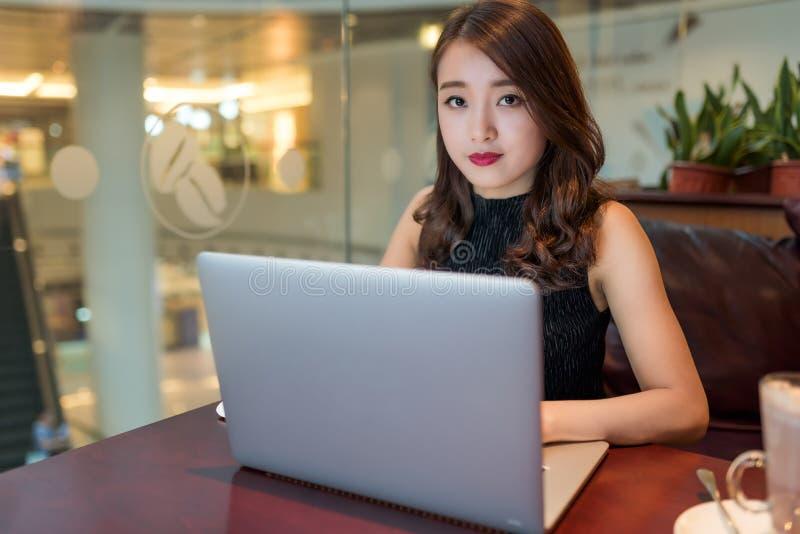 Mulher asiática que trabalha no portátil imagem de stock