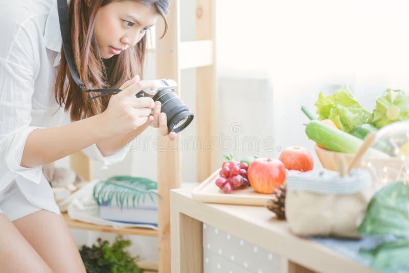 Mulher asiática que usa a câmera que toma imagens aos vegetais na cozinha da tabela fotos de stock