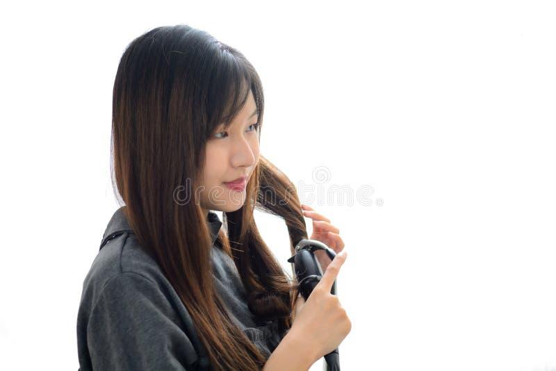 Mulher asiática que usa o cabelo de ondulação do ferro de ondulação Penteado e Haird foto de stock royalty free