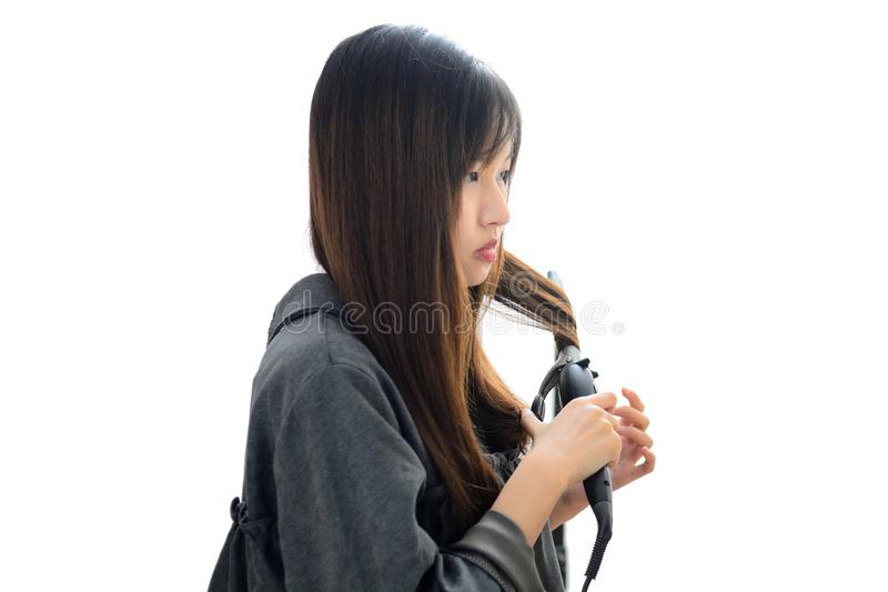 Mulher asiática que usa o cabelo de ondulação do ferro de ondulação Penteado e Haird fotografia de stock royalty free