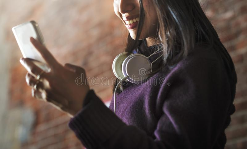 Mulher asiática que usa o dispositivo e fones de ouvido digitais foto de stock