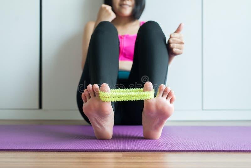 Mulher asiática que usa o elástico para a massagem que estica o dedo do pé com grampo e dor foto de stock