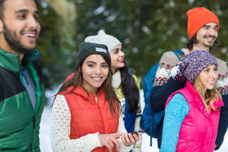 Mulher asiática que usa o inverno exterior de passeio do grupo esperto de Forest Happy Smiling Young People da neve do telefone imagem de stock royalty free