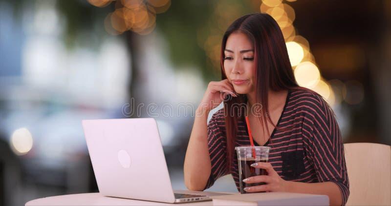 Mulher asiática que usa o portátil no restaurante fotos de stock
