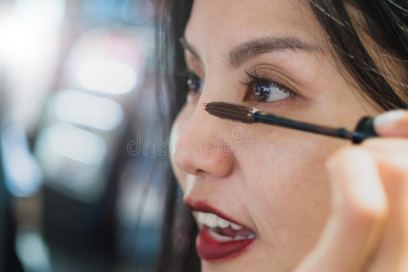 A mulher asiática que usa o rímel para compõe fotos de stock royalty free