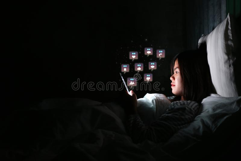 Mulher asiática que usa o smartphone para verificar meios sociais com o ícone imagens de stock