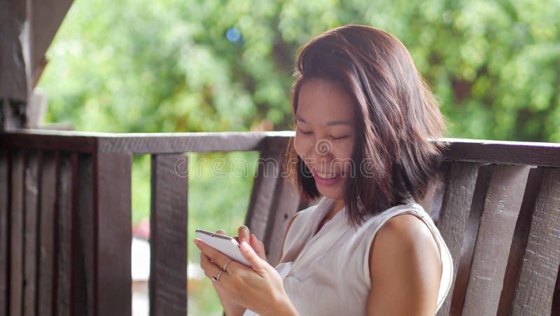 Mulher asiática que usa o sorriso feliz do telefone celular no jardim natural da natureza fotos de stock
