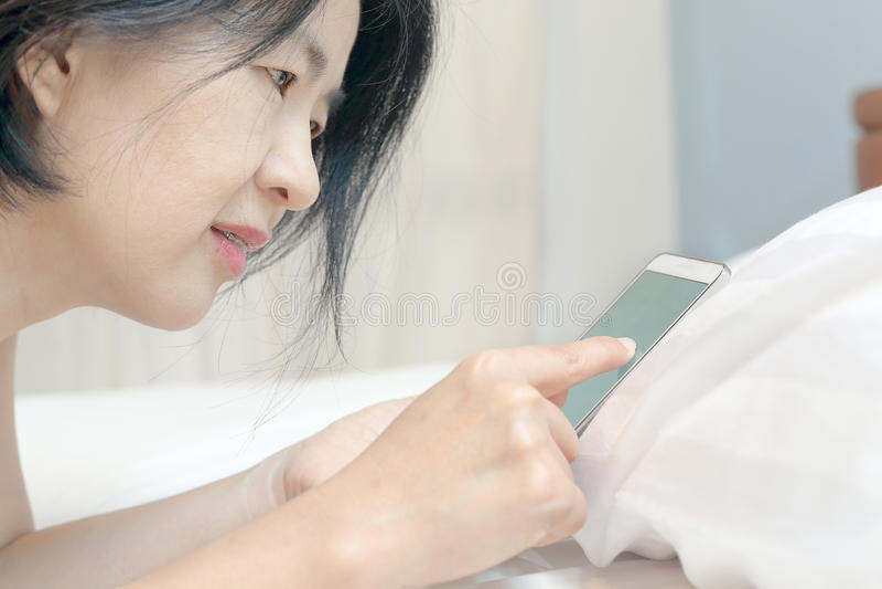 Mulher asiática que usa o telefone celular na cama foto de stock