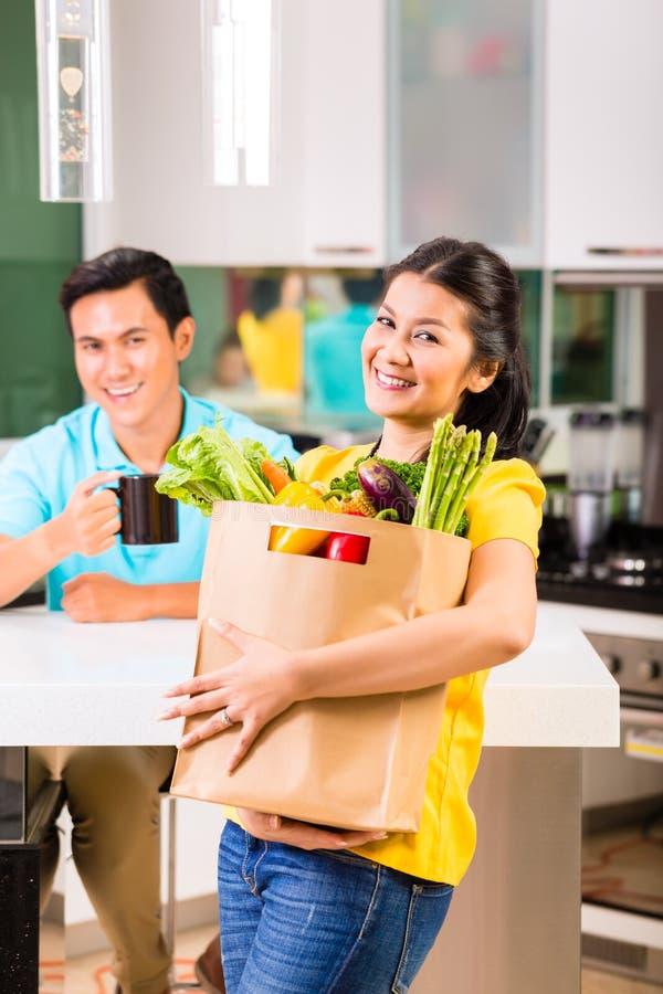 Mulher asiática que vem em casa das compras na mercearia fotografia de stock