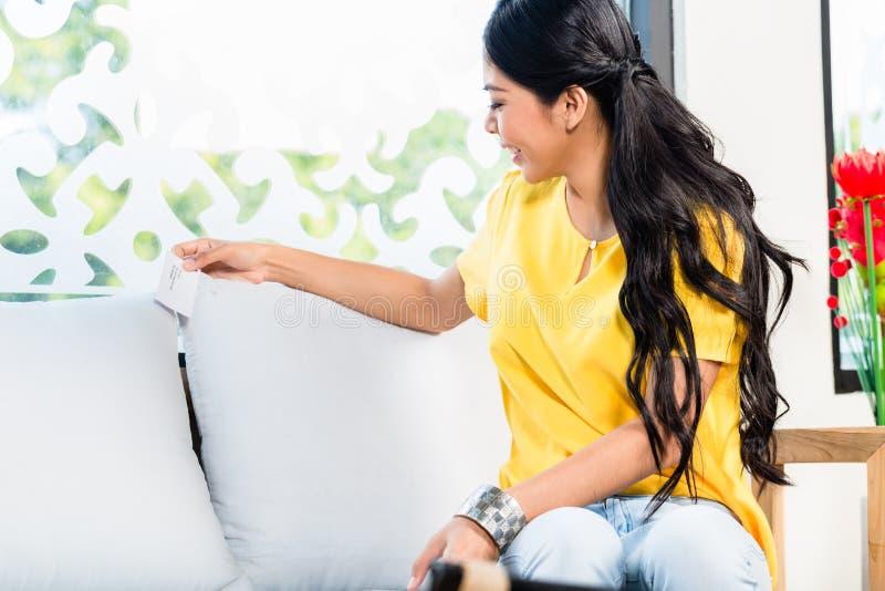 Mulher asiática que verifica o preço do sofá na loja imagens de stock