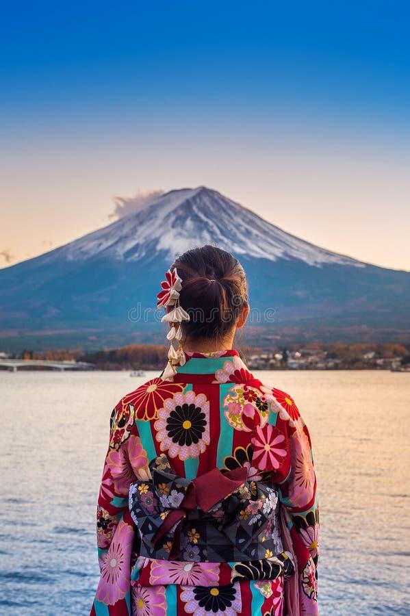 Mulher asiática que veste o quimono tradicional japonês na montanha de Fuji Por do sol no lago Kawaguchiko em Japão imagens de stock royalty free