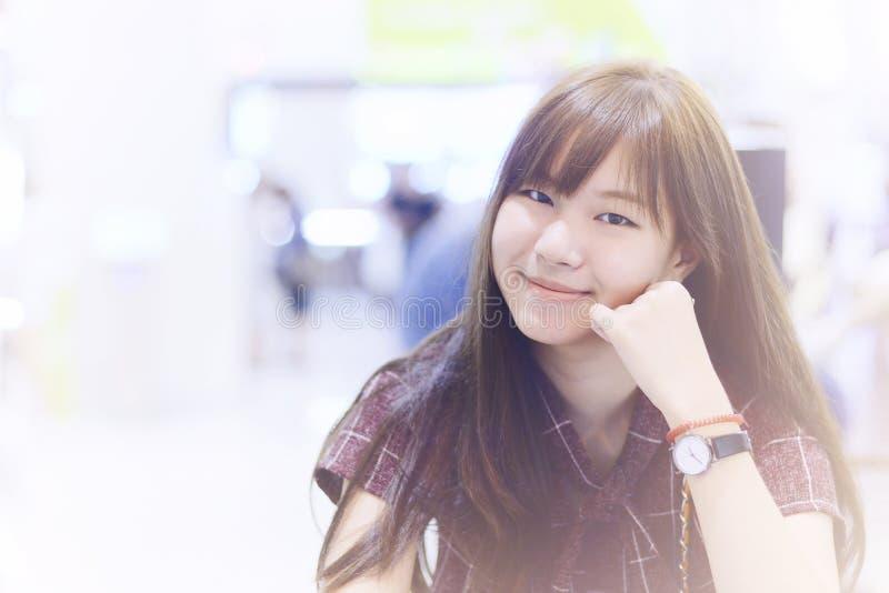A mulher asiática relaxa e sorri contra o escape claro e borra o backgrou imagem de stock