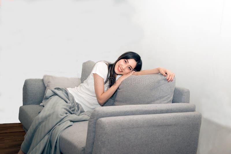 Mulher asiática relaxado e respiração de descanso fresca no sofá imagens de stock