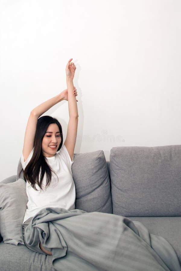 Mulher asiática relaxado e respiração de descanso fresca no sofá fotografia de stock royalty free
