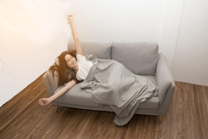Mulher asiática relaxado e respiração de descanso fresca no sofá em casa imagem de stock