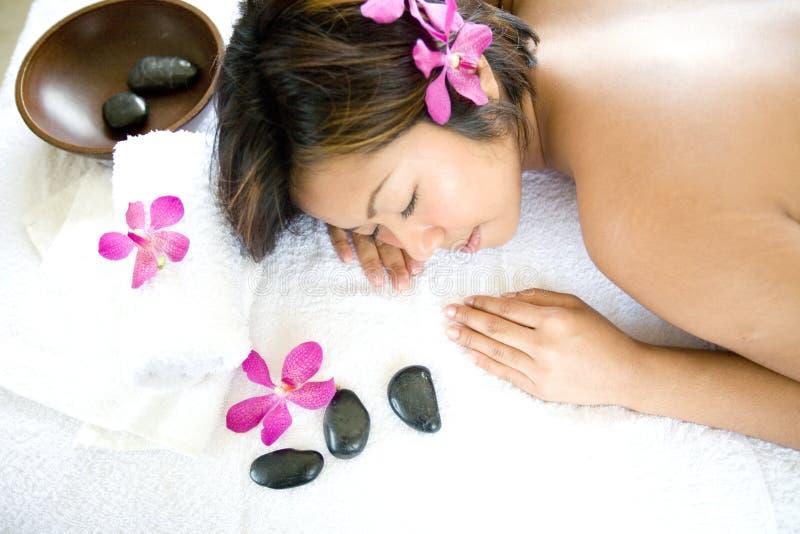 Mulher asiática restful na cama da terapia da massagem fotografia de stock