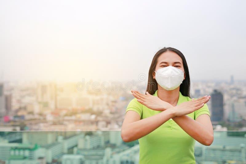 Mulher asiática séria que veste uma máscara da proteção com fatura do sinal X com seus braços parar PM 2 polui??o do ar 5 na cida imagem de stock royalty free