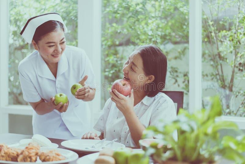 Mulher asiática sênior mãos segurando fruta fresca em casa,Enfermeira cuida,Conceito de comida saudável para idosos fotos de stock