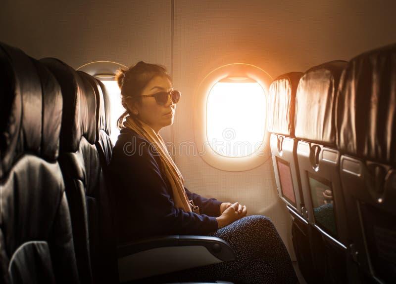 Mulher asiática só que senta-se ao lado do uso plano da janela para viajar fotografia de stock