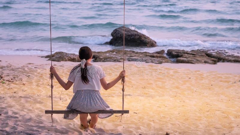Mulher asiática só que senta-se no balanço na praia foto de stock