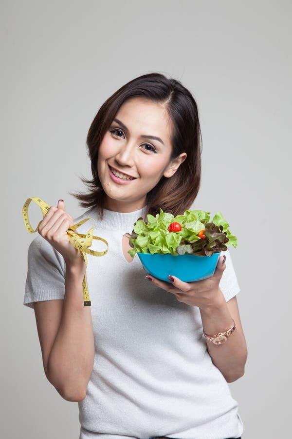 Mulher asiática saudável com fita e salada de medição imagem de stock royalty free