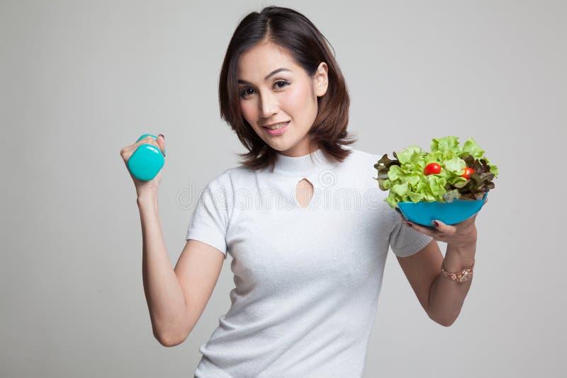 Mulher asiática saudável com pesos e salada imagem de stock