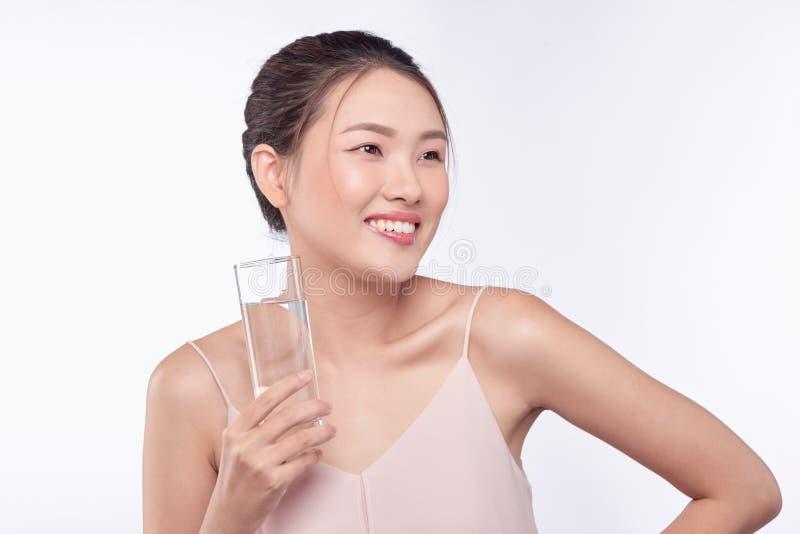 Mulher asiática saudável da beleza feliz nova que guarda a água de vidro com cara do smiley fotografia de stock royalty free