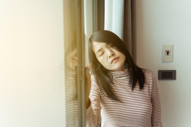 A mulher asiática seja uma dor de cabeça na cama após acorda na manhã, comprime a mulher em casa, problema de doenças do cérebro, foto de stock
