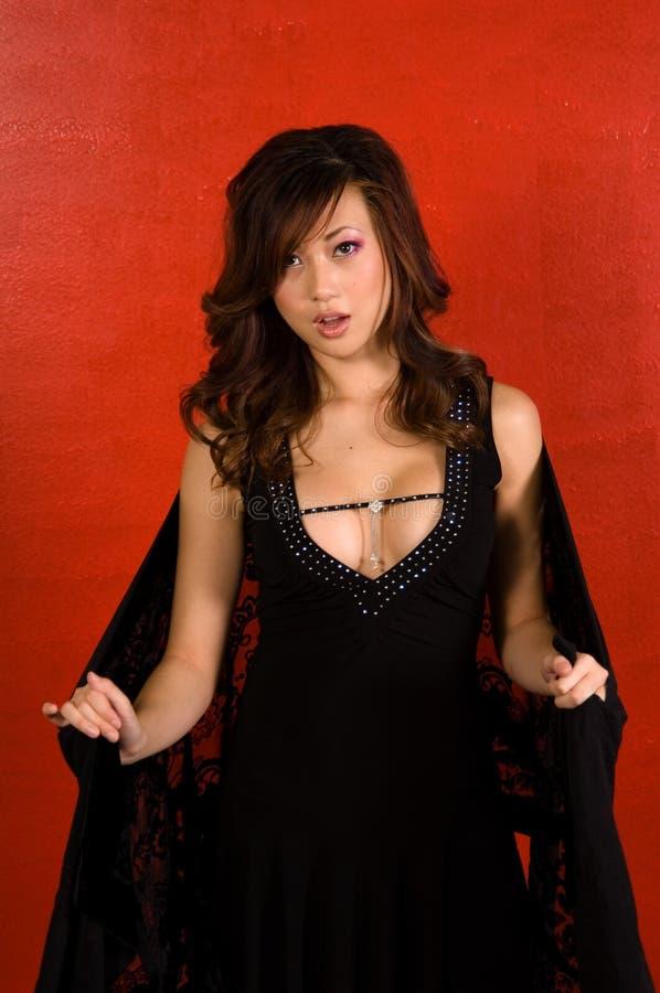 Mulher asiática 'sexy' na parede vermelha fotos de stock royalty free
